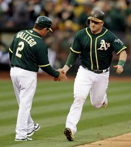 Oakland Athletics' Stephen Vogt, right, celebrates with third base coach Mike Gallego (2) after Vogt hit a two-run home run off Boston Red Sox pitcher Justin Masterson during the first inning of a baseball game Tuesday, May 12, 2015, in Oakland, Calif. (AP Photo/Ben Margot)