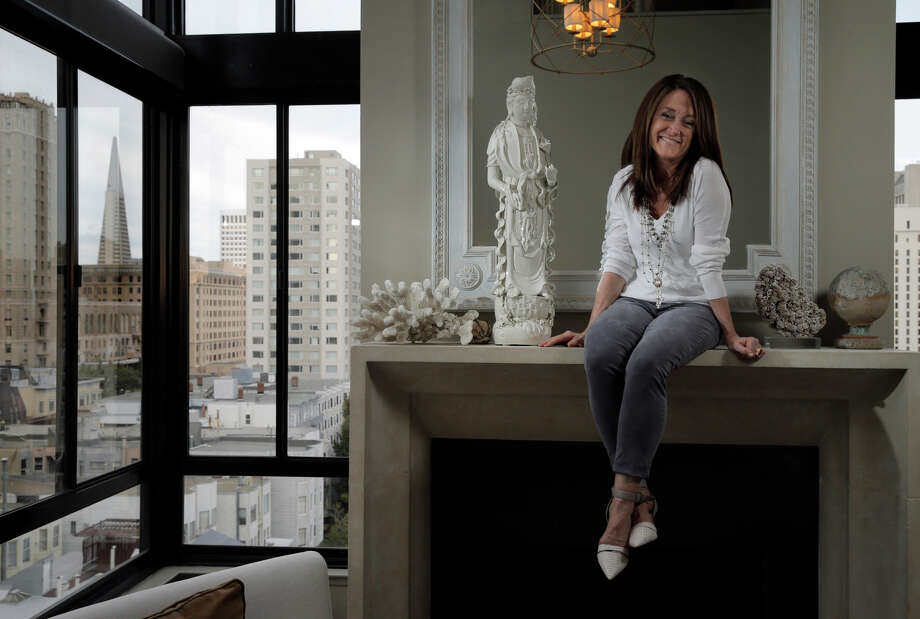 Kelly Hensley, owner of Leftovers consignment store, perches on the fireplace mantel of her S.F. penthouse apartment. Photo: Carlos Avila Gonzalez / Carlos Avila Gonzalez / The Chronicle / ONLINE_YES