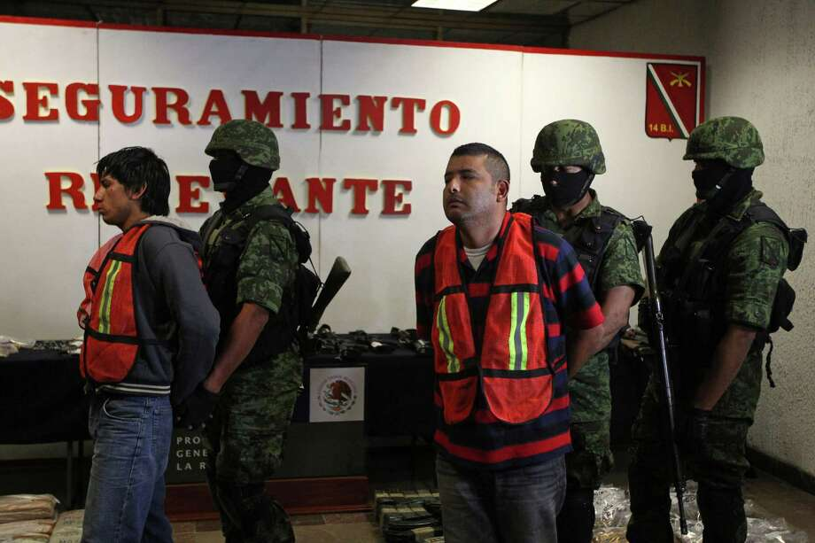 """Mexican army soldiers take away Jose Guadalupe Serna Padilla, aka """"El Zopilote"""" or """"The Vulture"""", center, and his alleged accomplice Oscar Pozos Jimenez, left, during a presentation to the press in Zapopan, on the outskirts of Guadalajara, Mexico Sunday March 18, 2012. According to the Mexican army, Padilla is an alleged top ranking member of the Jalisco New Generation Cartel. Click through to learn more about the CJNG, which has seized power in Mexico in recent years. Photo: Bruno Gonzalez, Associated Press / AP2012"""