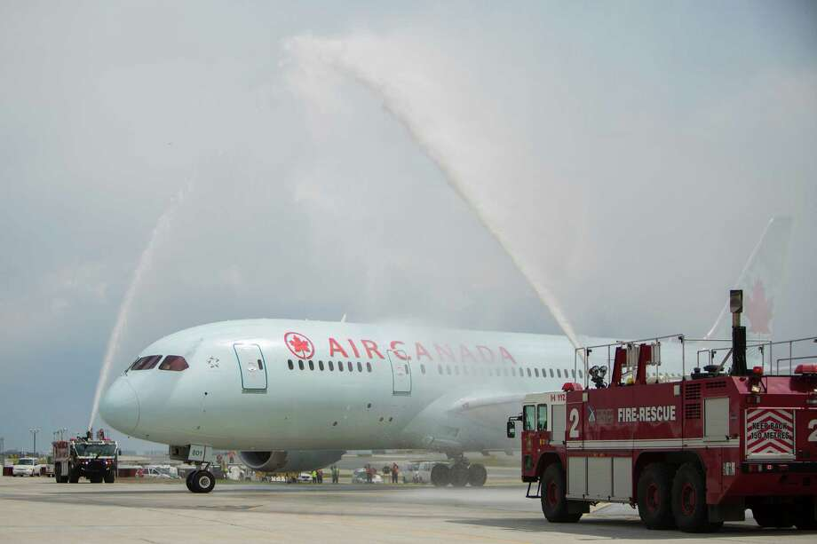 In this file photo, Air Canada's new 787 Dreamliner comes in for a water cannon salute at Toronto Pearson International Airport in 2014. Many were saluting an Air Canada pilot who diverted a jet to help save a dog recently. Speaking of dogs worth diverting a flight for, click through to see more images of cute and cuddly pups! Photo: Randy Risling, Getty Images / Toronto Star 2014
