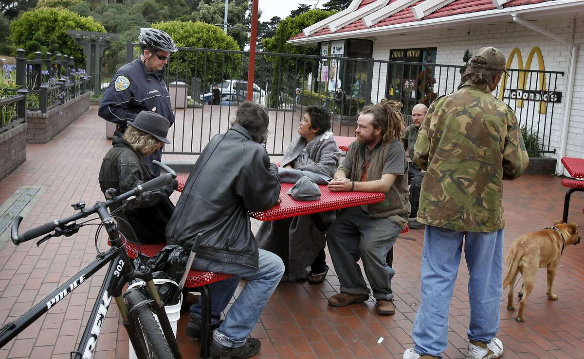 A Park Station police officer stopped to move along a group of people on the McDonalds property who had not bought any food Thursday August 26, 2010. Many of the young travelers who hang out near the end of Haight Street in San Francisco, Calif. believe the McDonalds there has removed the