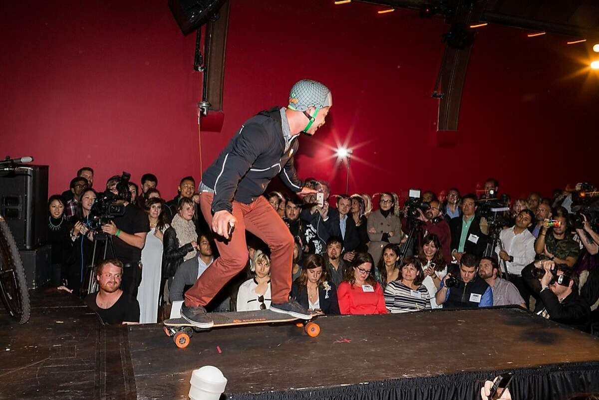 A man rides a Bossted Boards longboard across the runway as the crowd watches in awe at The Chapel during Silicon Valley Fashion Week? in San Francisco, Calif., Tuesday, May 12, 2015.