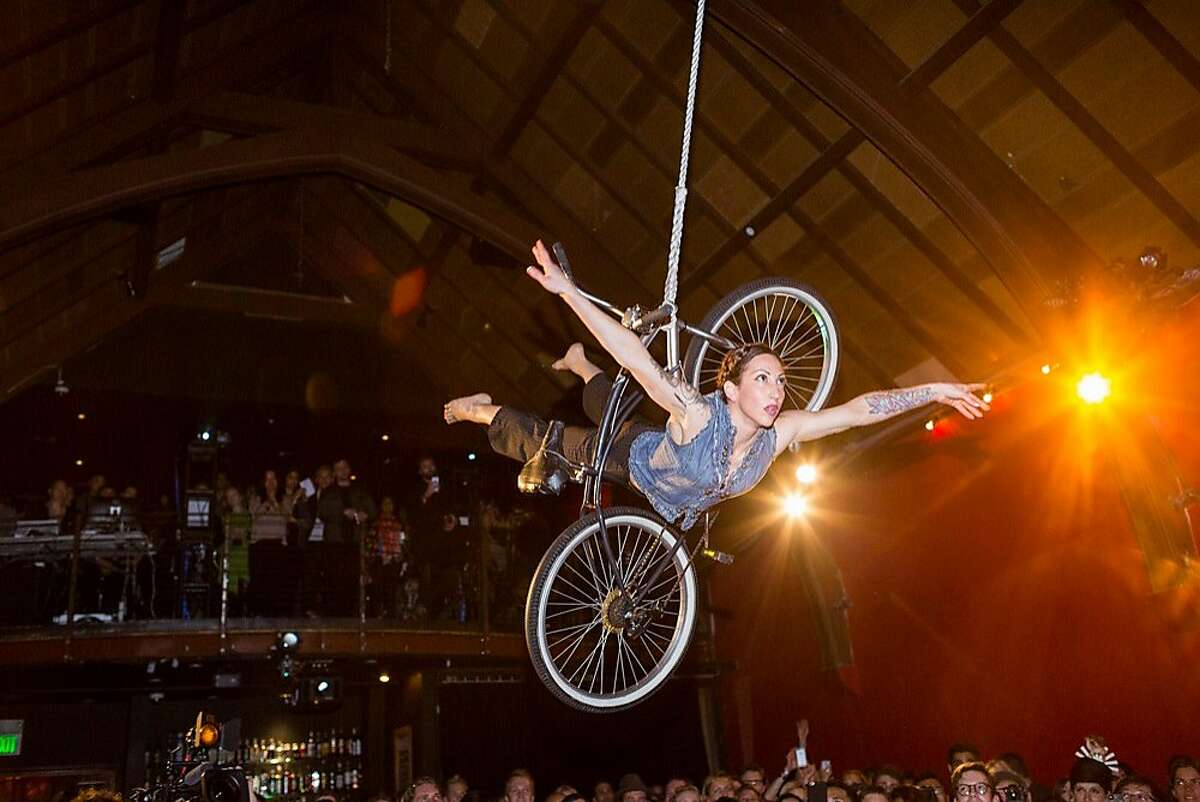 A trapeze artist danced with a bicycle dangling from the ceiling at The Chapel during Silicon Valley Fashion Week? in San Francisco, Calif., Tuesday, May 12, 2015.