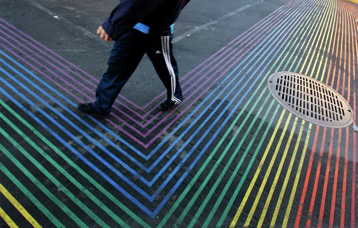 A man crosses the intersection of 18th and Castro streets as construction work nears completion on the Castro Street improvement project between Market and 19th streets in San Francisco, Calif. on Wednesday, Oct. 29, 2014. Among the improvements are wider sidewalks and crosswalks painted in rainbow colors.
