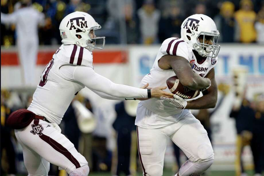 Texas A&M quarterback Kyle Allen, left, hands off to running back Tra Carson, right, in the second half of the Liberty Bowl NCAA college football game against West Virginia Monday, Dec. 29, 2014, in Memphis, Tenn. Texas A&M won 45-37. Photo: Mark Humphrey /Associated Press / AP