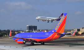 LOS ANGELES, CA - MAY 16, 2013: A Southwest Airlines Boeing 737 aircraft taxis toward its gate after landing, as a Hawaiian Airlines Boeing 767 passenger plane lands at Los Angeles International Airport (LAX) in Los Angeles, California.