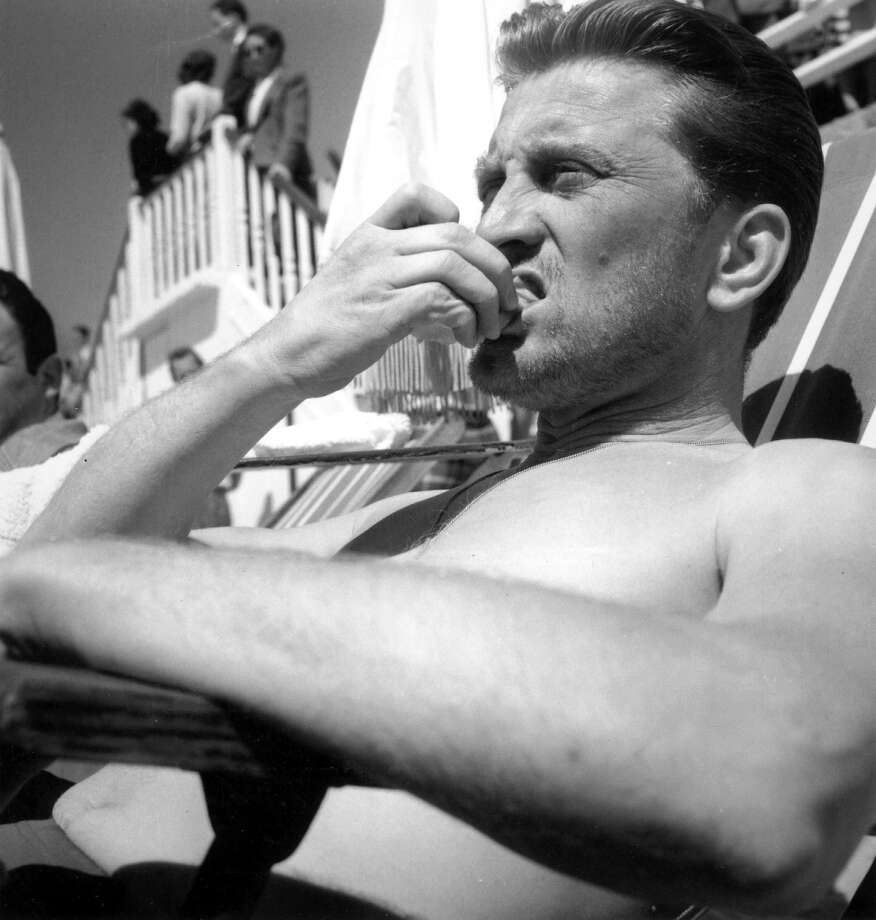American actor Kirk Douglas relaxes on the beach during the Cannes Film Festival, 18th April 1953. Photo: RDA, Getty Images