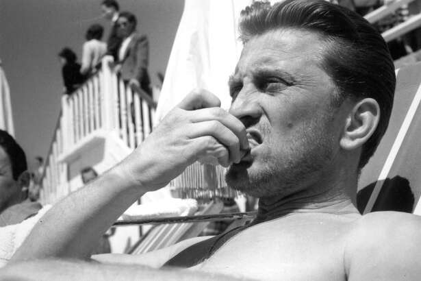 American actor Kirk Douglas relaxes on the beach during the Cannes Film Festival, 18th April 1953.