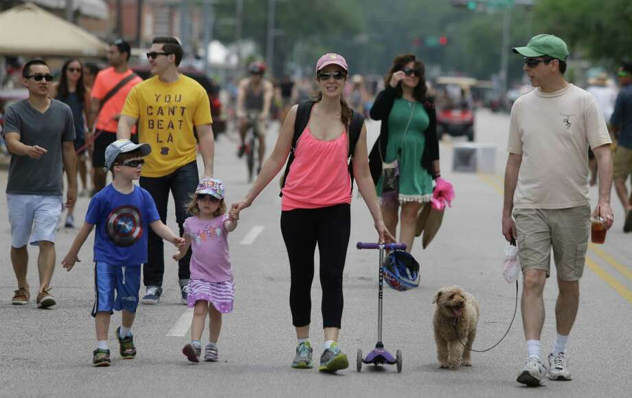 People walk along 19th Street during the Cigna Sunday Streets is the Heights! Sunday, April 26, 2015, in Houston. Traffic on 19th Street between Yale and Shepherd Street was re-routed to make way for visitors, residents and businesses to enjoy the community and one another through activities - walking, running, dancing, skating, cycling and more - in the street. Part bike tour, part walking tour, part block party, Cigna Sunday Streets was created to promote and improve the health of Houstonians and offers new economic opportunities for neighborhood commercial districts.  ( Melissa Phillip / Houston Chronicle ) Photo: Melissa Phillip, Staff / © 2015  Houston Chronicle
