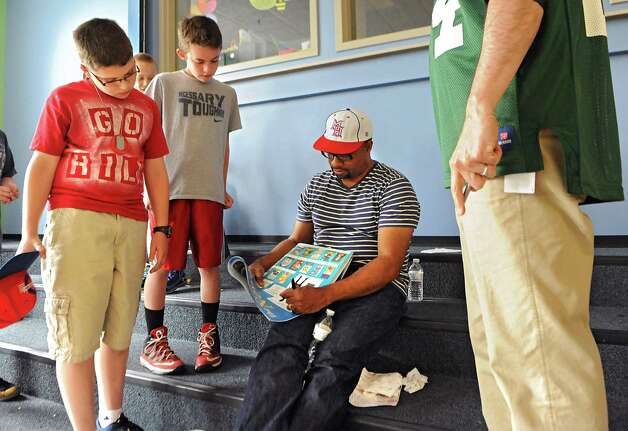 """Newbery Medal winning author Kwame Alexander signs autographs for 5th graders Ethan Wilkinson, 11, left, Jack Pomykaj, 11, and 5th grade teacher Sid Reischer, right, as he visits Castleton Elementary School on Wednesday, May 13, 2015 in Castleton, N.Y. Kwame won the 2015 Newbery Medal for best children's book in the country. Mr. Alexander's book """"The Crossover"""" is written entirely in poetry verse and tells the story of twin brothers on a junior high basketball team as they struggle with their father's declining health. (Lori Van Buren / Times Union) Photo: Lori Van Buren / 00031814A"""