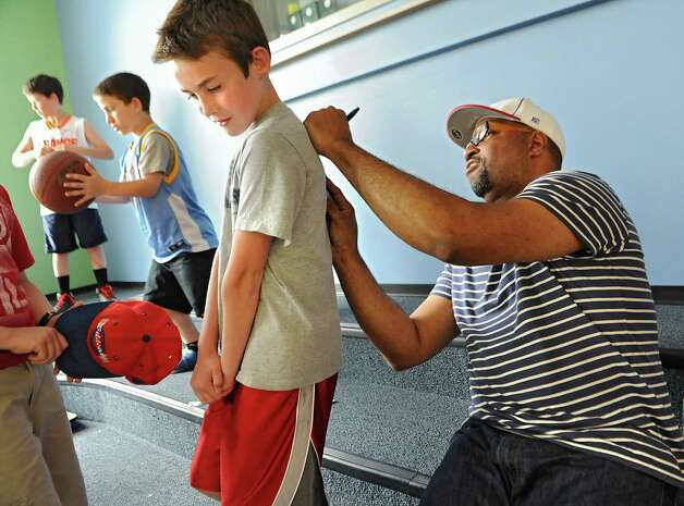 """Newbery Medal winning author Kwame Alexander signs an autograph on the shirt of 5th grader Jack Pomykaj, 11, as he visits Castleton Elementary School on Wednesday, May 13, 2015 in Castleton, N.Y. Kwame won the 2015 Newbery Medal for best children's book in the country. Mr. Alexander's book """"The Crossover"""" is written entirely in poetry verse and tells the story of twin brothers on a junior high basketball team as they struggle with their father's declining health. (Lori Van Buren / Times Union) Photo: Lori Van Buren / 00031814A"""