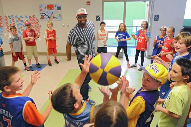 """Newbery Medal winning author Kwame Alexander plays a basketball game with 5th graders as he visits Castleton Elementary School on Wednesday, May 13, 2015 in Castleton, N.Y. Kwame won the 2015 Newbery Medal for best children's book in the country. Mr. Alexander's book """"The Crossover"""" is written entirely in poetry verse and tells the story of twin brothers on a junior high basketball team as they struggle with their father's declining health. (Lori Van Buren / Times Union) Photo: Lori Van Buren / 00031814A"""
