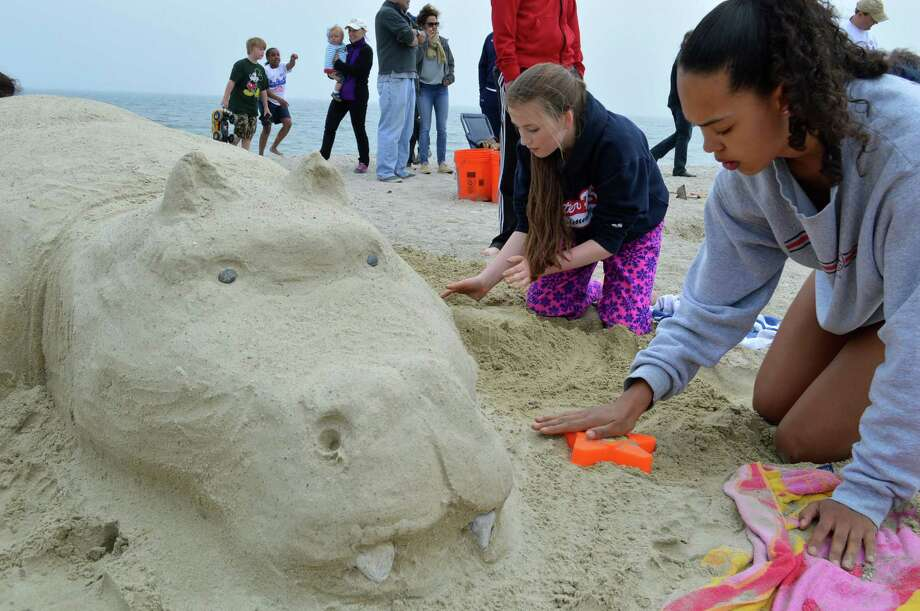 Honor Heisler, 14, left, and Isabella Jagenverg, 14, both of Westport, fashioned a creature from the sands of Compo Beach at the Castles in the Sand contest Saturday. Photo: Jarret Liotta / Westport News