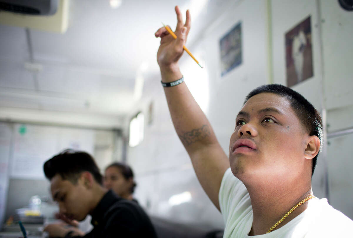 Marcus Valino raises his hand during a session in a trailer in the Gleneagles parking lot that serves as a classroom for the program.