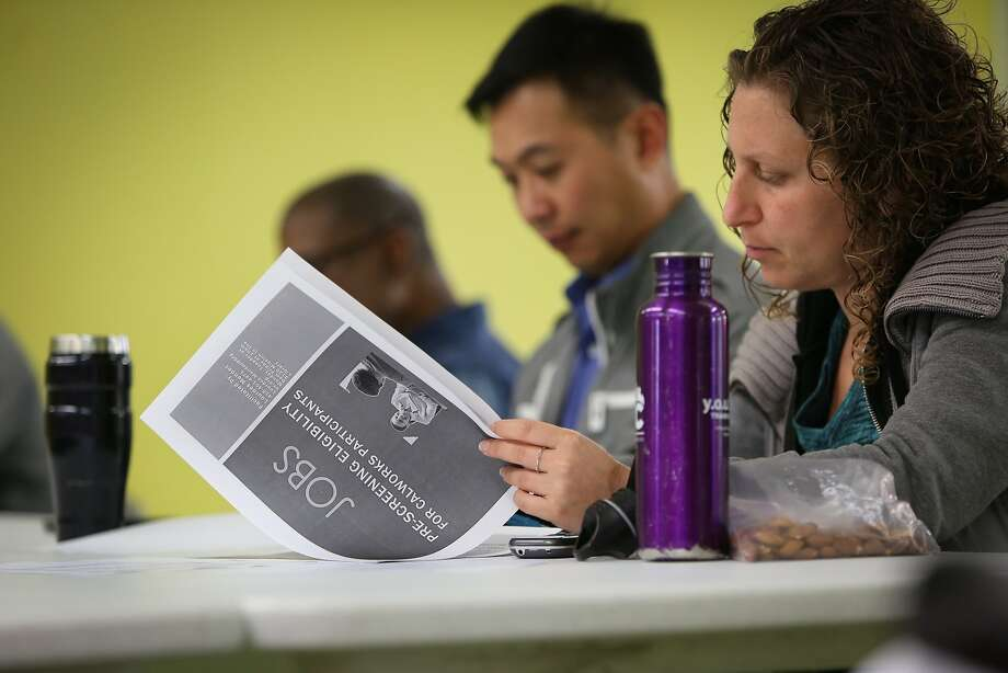 In this 2015 photo, people review a packet from Jobs Now, a program run by the Human Services Agency. Photo: Amy Osborne, The Chronicle