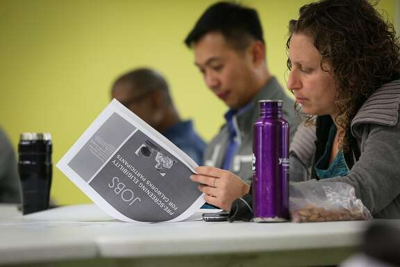 Amanda Sommers and Wilson Ho Yin Cheh review a packet from Jobs Now, a program by Human Services Agency, helps businesses and job seekers connect and fulfill employment opportunities in San Francisco on Wednesday, May 13, 2015.