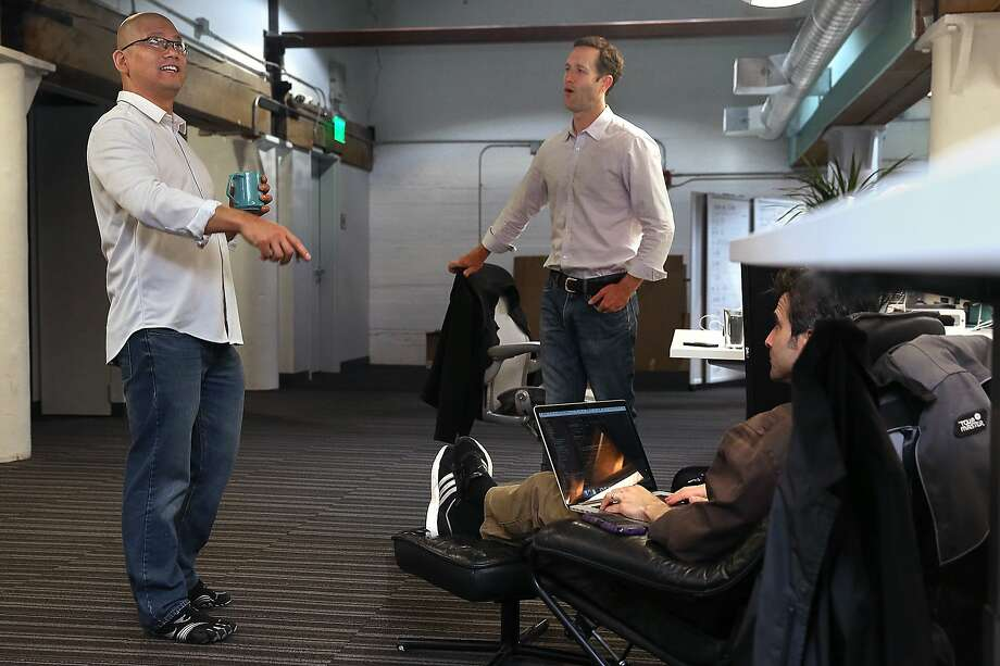 CEO and co-founder Yee Lee (left) talks with vice president of marketing   and product management Bill Onderdonk (right) and vice present of growth and co-founder Hugh Olliphant (seated at right) at Vouch in San Francisco, California, on Wednesday, May 13, 2015.  Vouch helps customers with creditworthiness for loans by helping them build a trusted network. Photo: Liz Hafalia, The Chronicle