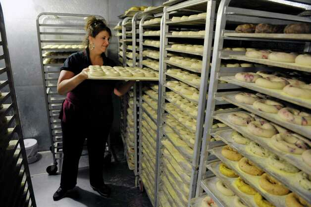 Toniann Avery co-owner of Bagels and Bakes slides in a rack of uncooked bagels in the cooler on Thursday, May 7, 2015, in Schenectady, N.Y.  The cooler holds the bagels for the next day.  Avery said that on average they are making up 150 dozen bagels a day but some days they are producing 250 dozen.  (Paul Buckowski / Times Union) Photo: PAUL BUCKOWSKI / 00031740A