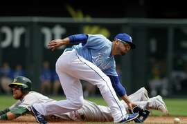 Oakland Athletics' Ben Zobrist, left, steals second base while Kansas City Royals second baseman Omar Infante, right, fields a throw during the first inning of a baseball game at Kauffman Stadium in Kansas City, Mo., Sunday, April 19, 2015. (AP Photo/Orlin Wagner)