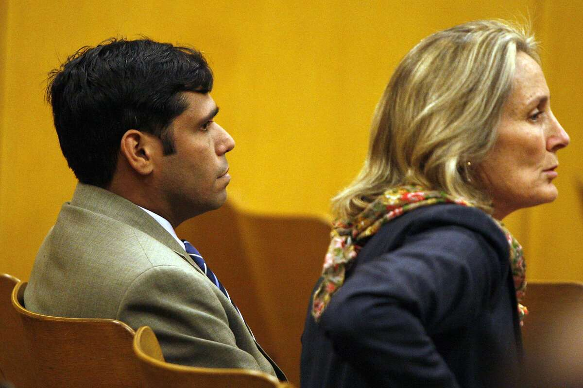 Enrique Pearce, left, and his lawyer Eileen Burke listen in to the prosecutor inside the courtroom at the Hall of Justice, Wednesday, May 13, 2015, in San Francisco, Calif. Pearce a political consultant for S.F. Mayor Ed Lee, was arraigned on child porn possession charges. He pleaded not guilty. Pearce was taken into custody after being deemed a public safety risk by the prosecutor. Bail was set to $400,000.