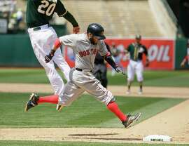 Boston's Dustin Pedroia safely reaches first base when shortstop Marcus Semien's throw to Mark Canha (left) is high.
