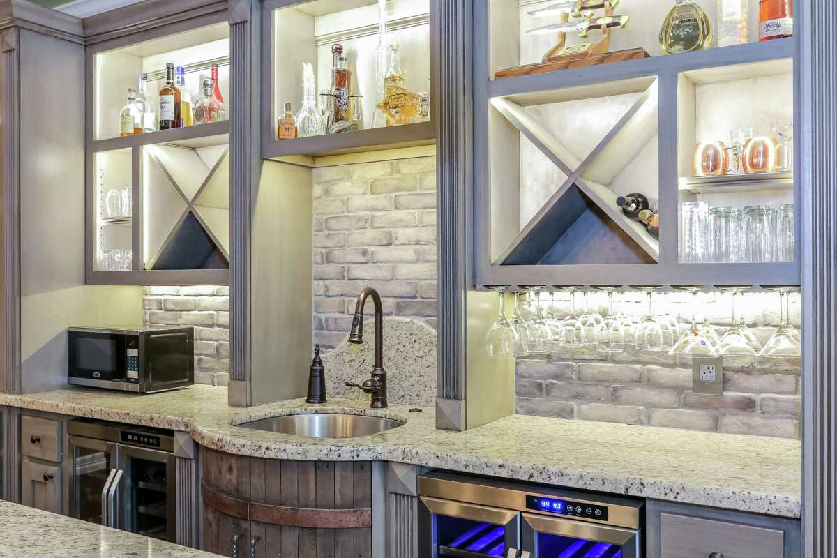The custom-made sink is shaped to look like a barrel. LED lighting illuminates the shelves, making the kitchen appear to glow.