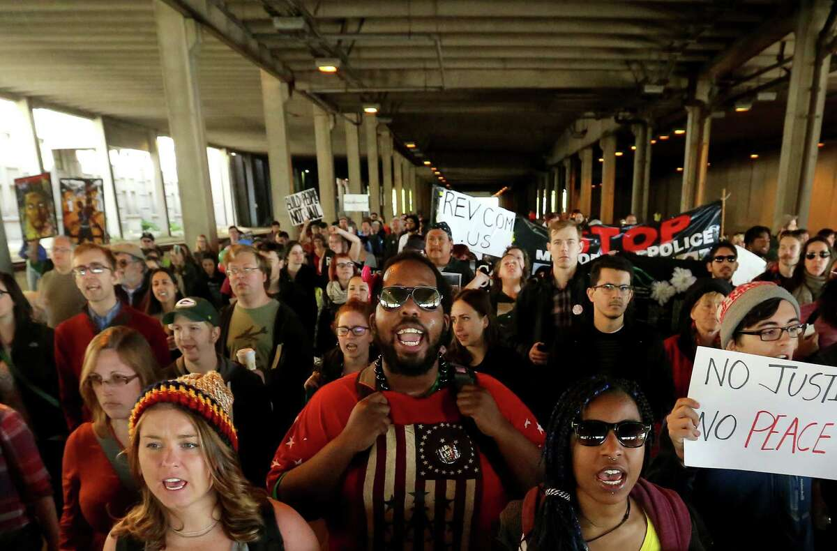 Protesters pass through a tunnel under the Monona Terrace Convention Center while making their way the Dane County Courthouse in Madison, Wis.