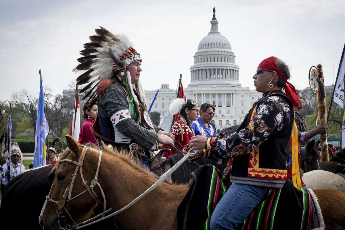 Members of the Cowboy and Indian Alliance (CIA), a group of ranchers, farmers and indigenous leaders, ride horses past the U.S. Capitol during a protest against the Keystone XL pipeline on the National Mall in Washington, D.C., U.S., on Tuesday, April 22, 2014. TransCanada Corp. is awaiting a U.S. permit to build the northern leg of Keystone XL, which would supply U.S. Gulf Coast refineries with crude from Alberta's oil sands. Because it crosses an international boundary, the proposal requires State Department approval. Photographer: Pete Marovich/Bloomberg