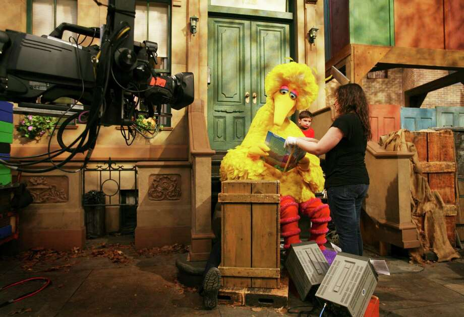 """Michelle Hickey helps Caroll Spinney, in his Big Bird persona, read to Connor Scott on a 2008 """"Sesame Street"""" segment. A new film offers an affectionate portrait of Spinney. Photo: MARK LENNIHAN / Mark Lennihan / Associated Press 2008 / AP"""