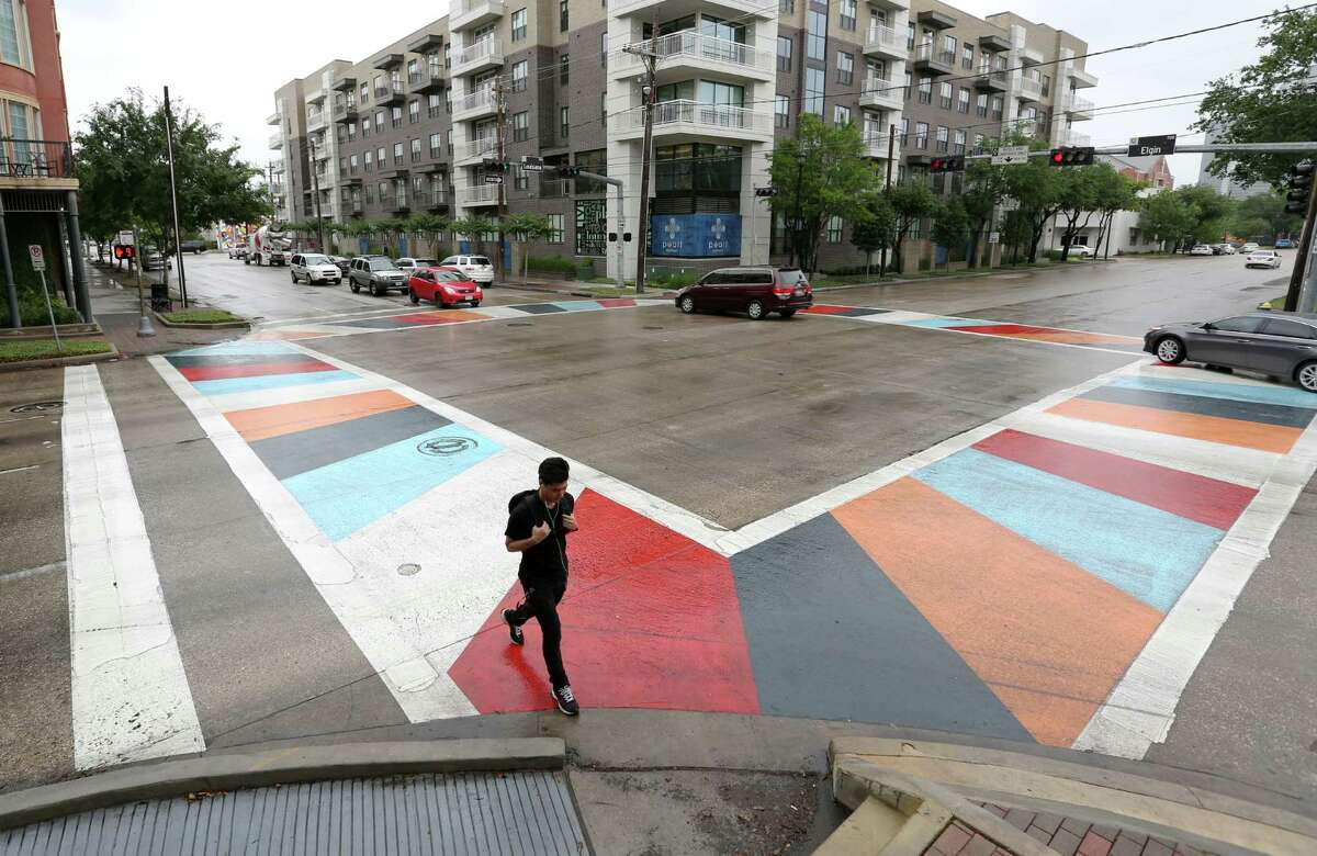 A pedestrian crosses at a new artistic crosswalk at the intersection of Elgin Street and Louisiana Street on Tuesday.