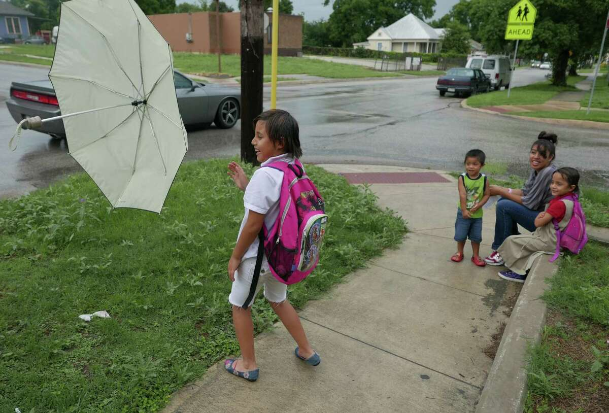 LEFT: Emilee Lopez plays with an umbrella by her siblings, Lilly and Miles, and mother, Perla, at Hays Street and Pine Street.
