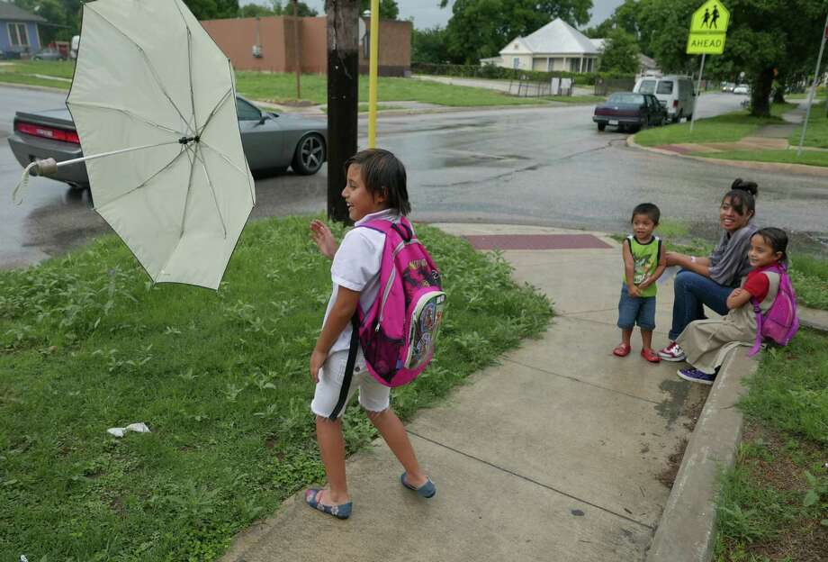 Emilee Lopez plays with an umbrella by her siblings, Lilly and Miles, and mother, Perla, at Hays Street and Pine Street. Photo: Billy Calzada /San Antonio Express-News / San Antonio Express-News