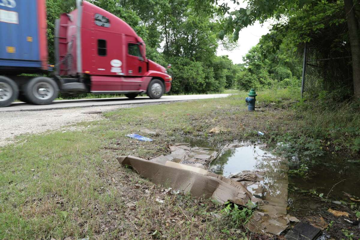 A 18 wheeler travels down Kirkpatrick blvd in Houston's 5th ward passing dumped garbage on the street side, Wednesday May 13, 2015.