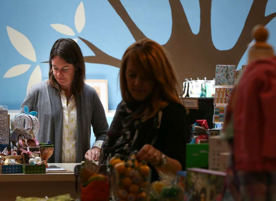 Elizabeth Leu, owner of Fiddlesticks in Hayes Valley, wraps a gift order while a customer browses the store on Wednesday, May 13, 2015 in San Francisco, Calif.  Photo: Amy Osborne, The Chronicle