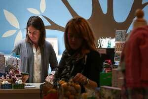 Elizabeth Leu, owner of Fiddlesticks in Hayes Valley, wraps a gift order while a customer browses the store on Wednesday, May 13, 2015 in San Francisco, Calif. Leu has been trying for weeks to hire a sales associate for her boutique children's clothing store.