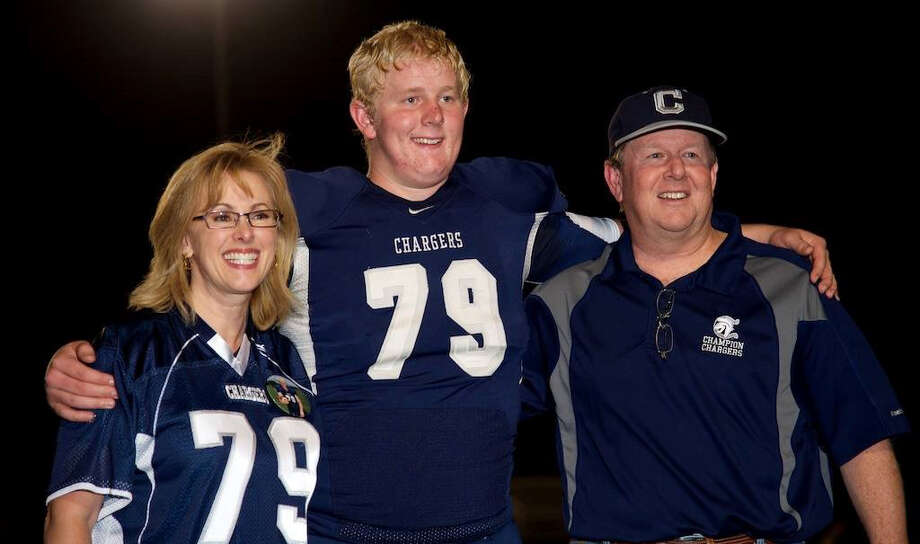 Patty Curney (left), Zeke Curney (center) and John Curney pose before a Boerne Champion football game in 2014. Curney, an avid Champion supporter and part-time announcer at baseball games, died on May 1. Photo: Courtesy Photo / Ralph Mawyer Photography