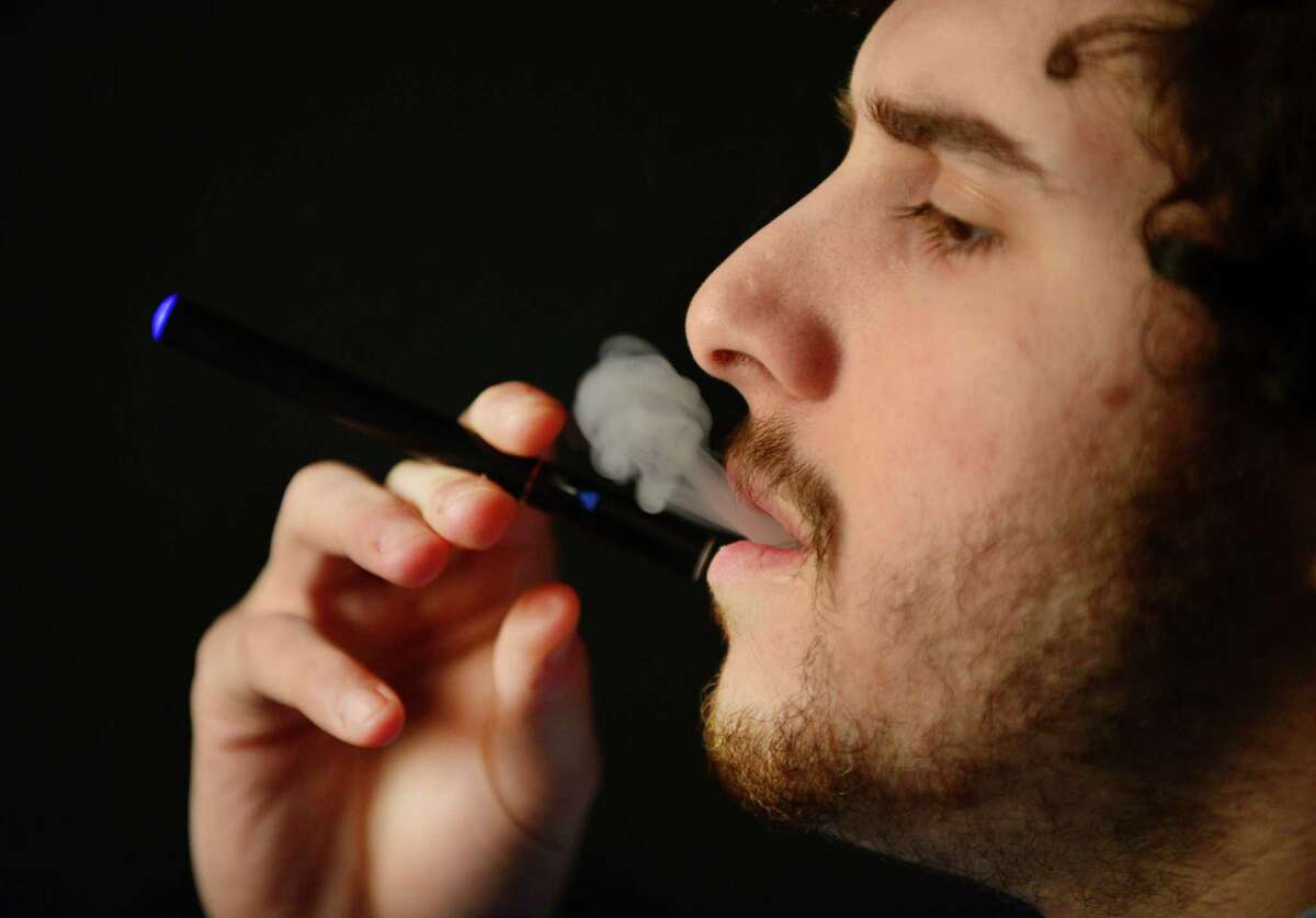 An e-cigarette is smoked Thursday, Feb. 6, 2014, at the Times Union photo studio in Colonie, N.Y. (Will Waldron/Times Union archive)