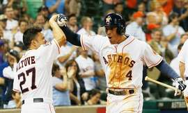HOUSTON, TX - MAY 13:  Jose Altuve #27 of the Houston Astros greets teammate George Springer #4 of the Houston Astros after Springer hit a solo home run in the eighth inning of their game against the San Francisco Giants  at Minute Maid Park on May 13, 2015 in Houston, Texas.  (Photo by Scott Halleran/Getty Images)