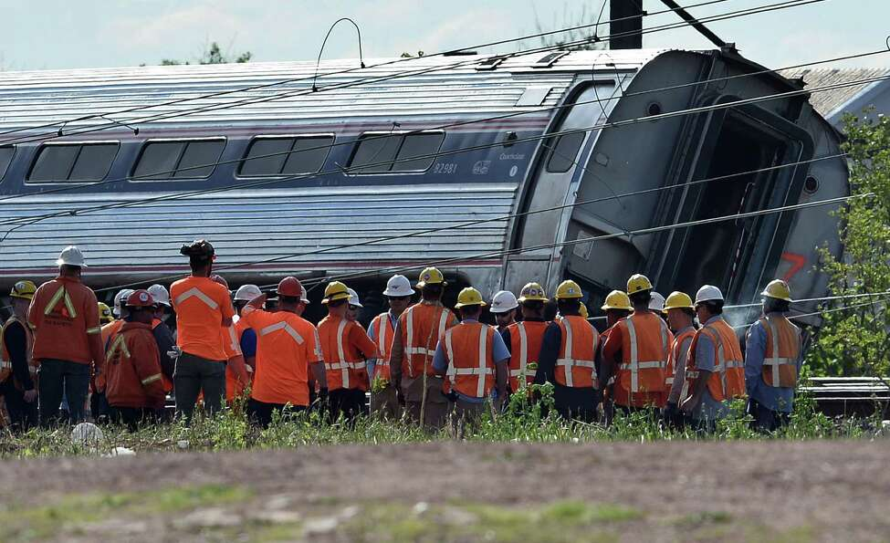 TOPSHOTS Rescuers gather around a derailed carriage of an Amtrak train in Philadelphia, Pennsylvania, on May 13, 2015. Rescuers on May 13 combed through the mangled wreckage of a derailed train in Philadelphia after an accident that left at least six dead, as the difficult search for possible survivors continued. AFP PHOTO/JEWEL SAMADJEWEL SAMAD/AFP/Getty Images ORG XMIT: 554054473