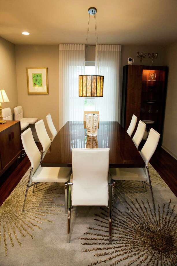 White leather-and-chrome dining chairs set off the sleek black table in the dining room of Gerry Garcia and Jack Elsbree. Photo: Photos By Carolyn Van Houten /San Antonio Express-News / 2015 San Antonio Express-News