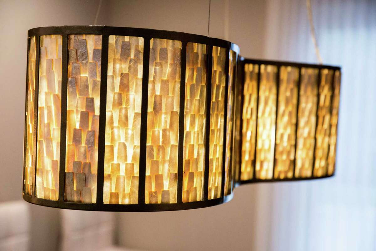 A light fixture reflects the midcentury modern style of the home and its furnishings.