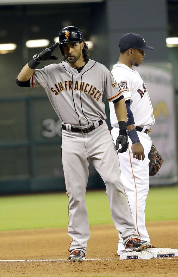 San Francisco Giants' Angel Pagan, left, salutes toward the dugout after hitting a triple as Houston Astros third baseman Luis Valbuena, right, looks toward the pitcher during the fifth inning of a baseball game Wednesday, May 13, 2015, in Houston. (AP Photo/David J. Phillip) Photo: David J. Phillip, Associated Press