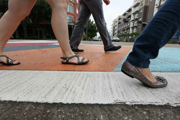 Pedestrians cross at a new artistic crosswalk at the intersection of Elgin Street and Louisiana Street Tuesday, May 12, 2015, in Houston.