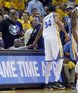 Boxer Floyd Mayweather, Jr. fist bumps Golden State Warriors' Shaun Livingston in 4th quarter of Warriors' 98-78 win over Memphis Grizzlies during Game 5 of NBA Playoffs' Western Conference Semifinals at Oracle Arena in Oakland, Calif., on Wednesday, May 13, 2015.