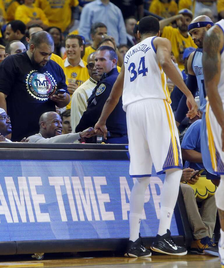 Boxer Floyd Mayweather, Jr. fist bumps Golden State Warriors' Shaun Livingston in 4th quarter of Warriors' 98-78 win over Memphis Grizzlies during Game 5 of NBA Playoffs' Western Conference Semifinals at Oracle Arena in Oakland, Calif., on Wednesday, May 13, 2015. Photo: Scott Strazzante, The Chronicle