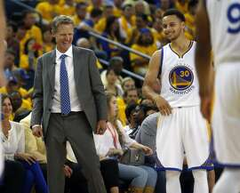 Golden State Warriors' Head Coach Steve Kerr and Stephen Curry share a light moment in 4th quarter of 98-78 win over Memphis Grizzlies during Game 5 of NBA Playoffs' Western Conference Semifinals at Oracle Arena in Oakland, Calif., on Wednesday, May 13, 2015.