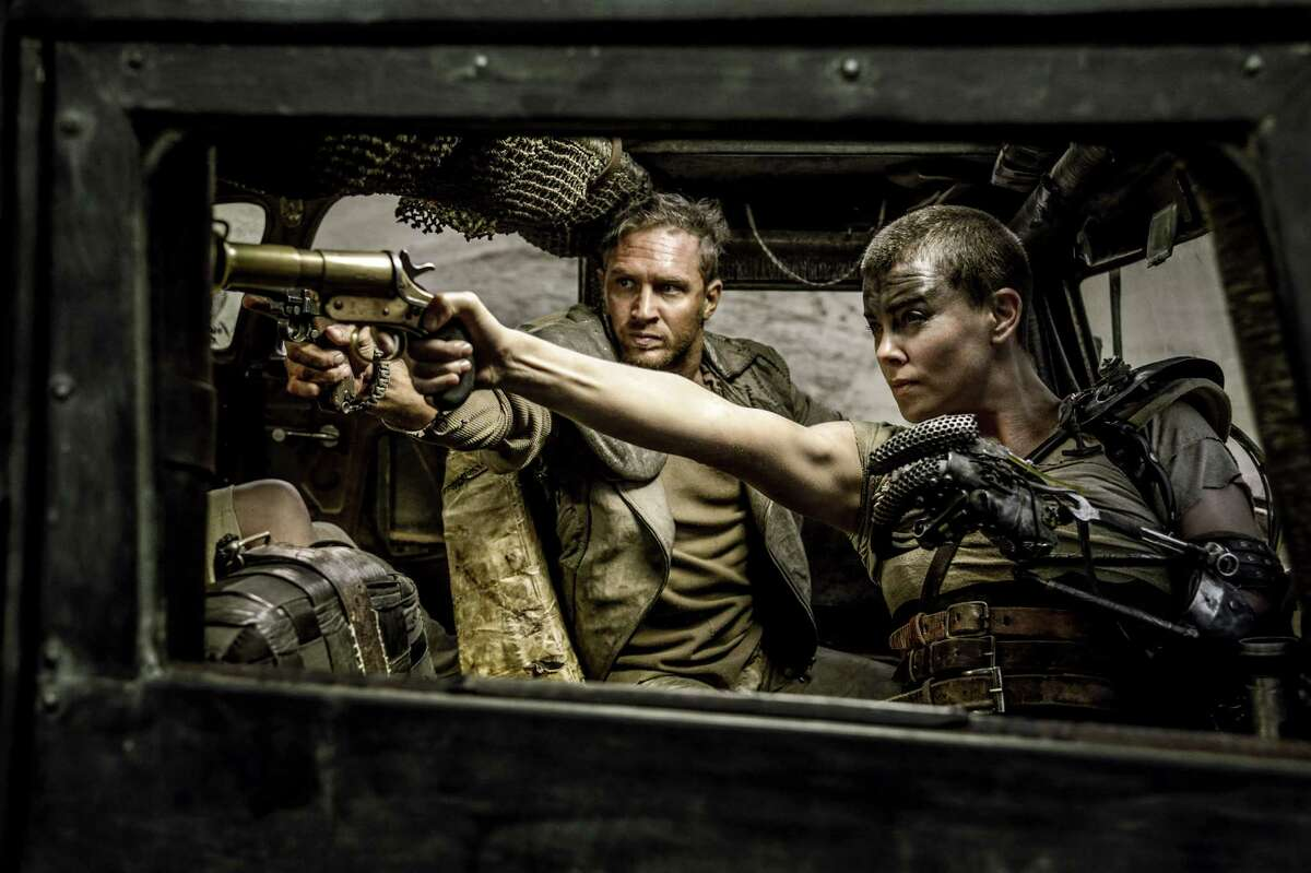 """This photo provided by Warner Bros. Pictures shows Tom Hardy, center, as Max Rockatansky and Charlize Theron, right, as Imperator Furiosa in Warner Bros. Pictures?' and Village Roadshow Pictures?' action adventure film, ?""""Mad Max:Fury Road,"""" a Warner Bros. Pictures release. (Jasin Boland/Warner Bros. Pictures via AP)"""
