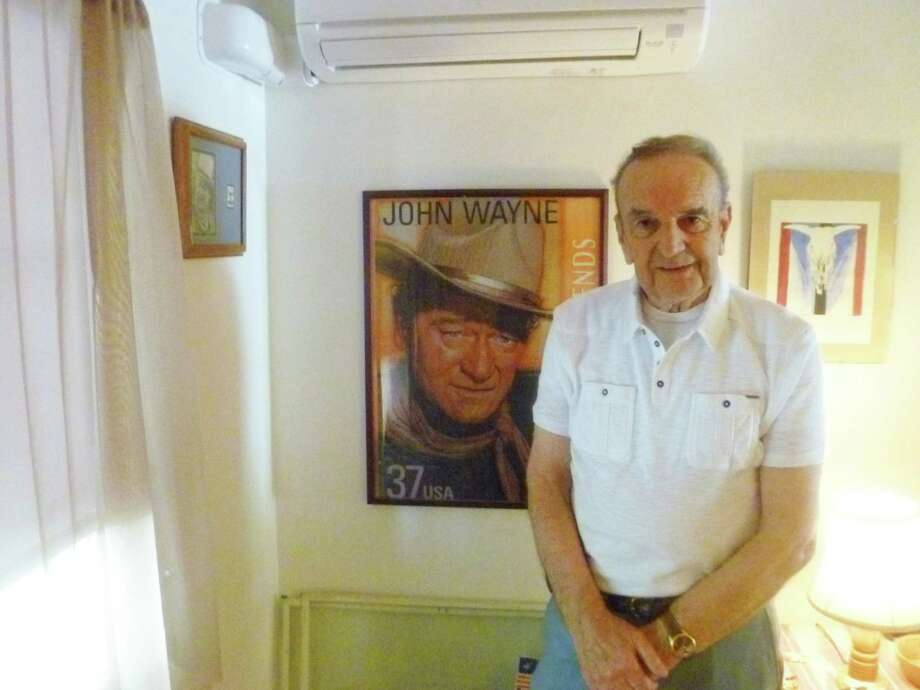 Bill Grega, 80, a former Darien police office, poses next to a framed poster depicting the John Wayne: Legends of Hollywood 2004 U.S. Postal Service stamp. Grega Has been an avid Wayne fan for nearly 70 years. Photo: Martin Cassidy / Darien News