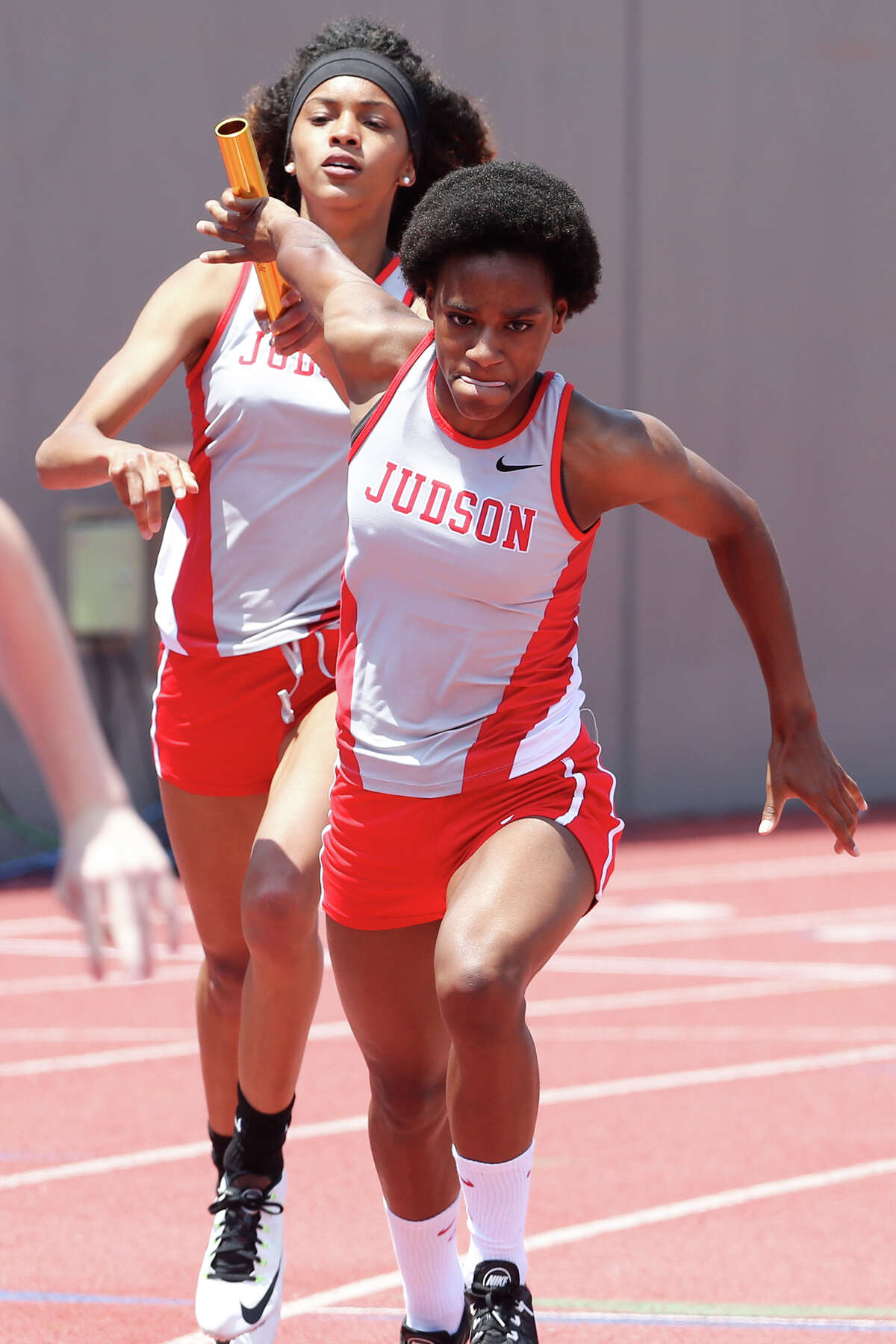 Judson's Kiara Pickens (right) takes the handoff from Mariah Kuykendoll to start the third leg of the Class 6A 800-meter relay during the Region IV-5A and Region IV-6A track and field meet at Alamo Stadium on May 2, 2015. Judson won the event with a time of 1 minute, 37.38 seconds, beating its Regional record set in 2014.