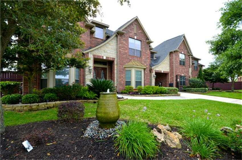Fulshear: Five-bedroom Cross Creek Ranch home has a sitting area and fireplace in the master suite; two upstairs game rooms and a media room; and a covered patio with pool outside. 5,789 square feet